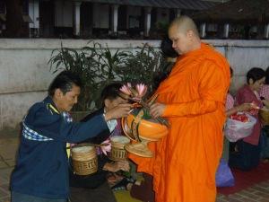 Für die Laoten ist es eine Ehre, den Mönchen eine Essensspende zu überreichen.